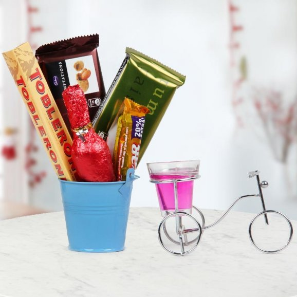 hamper of Chocolates and an aromatic Candle placed beautifully in a cycle-shaped stand