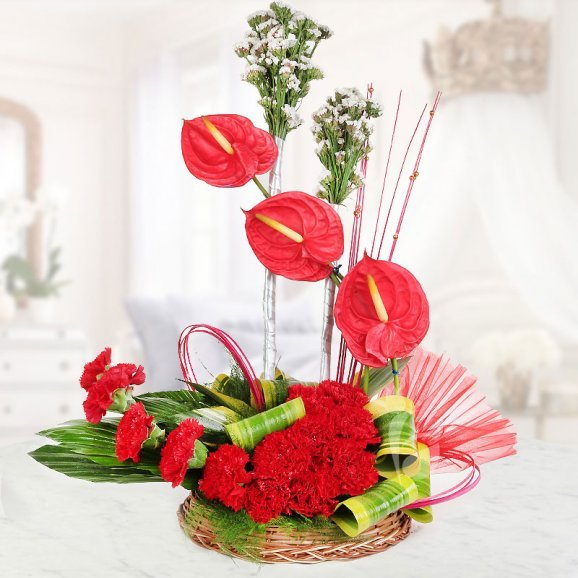 An arrangement of 13 Red Carnations along with 3 Red Anthuriums in Basket