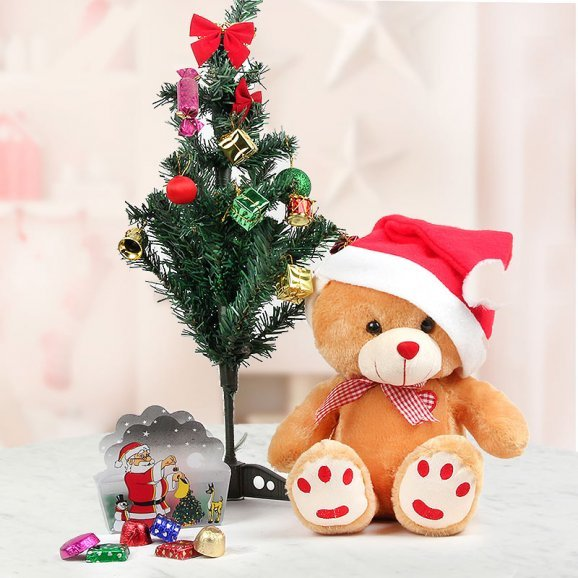 Teddy with stylish Santa cap and a red color bow Along with 2 feet artificial christmas tree, a beautifuk Santa Card Box and Christma chocolates