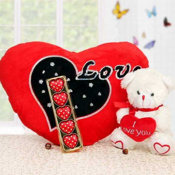 Chocolates and teddy alongwith a heart shaped cushion