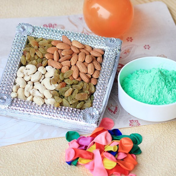 A combo having a pack of balloons a pack of dry fruits and one pack of herbal gulal