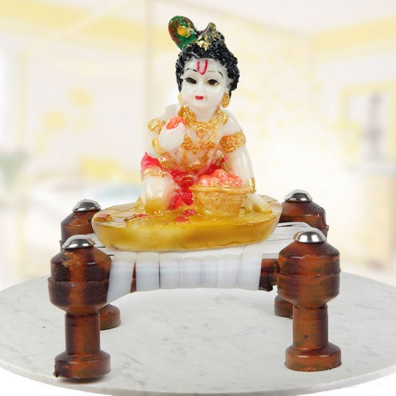 Krishna on the chowki eating Modak