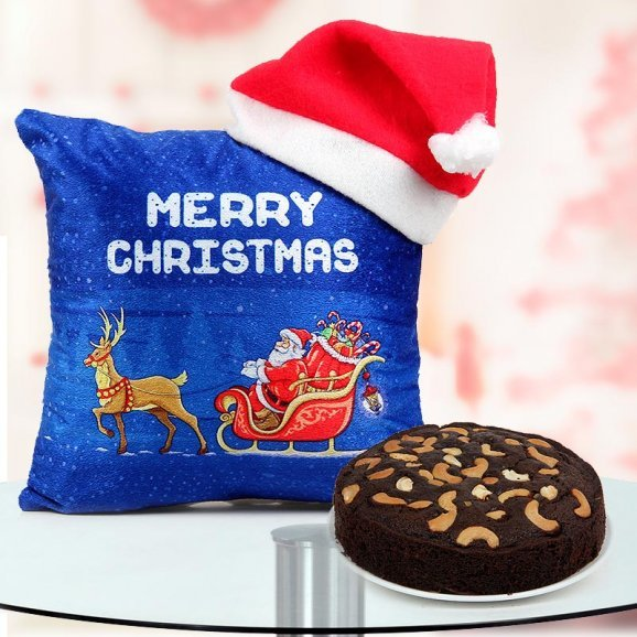 A 12x12 inches digitally printed 'Merry Christmas' Cushion featuring Santa on his sleigh, a Santa Cap, and a 1/2 kg freshly baked Plum Cake