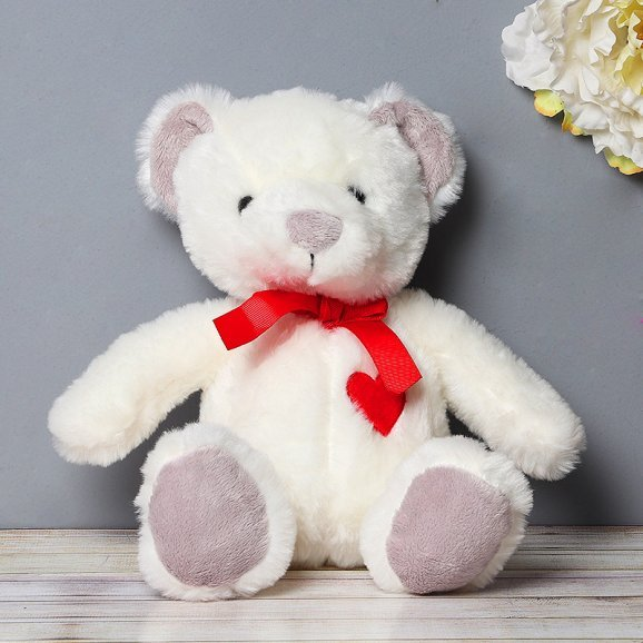 White Teddy Wearing a Red Bow