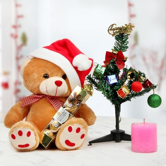 Combo of 12 inches snuggly teddy bear adorning the Classic Santa hat, a 1 feet Christmas tree and a scented pink candle in addition to 4 Ferrero Rocher