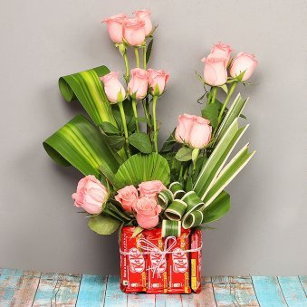 Arrangement of Roses with Chocolates in a Glass Vase