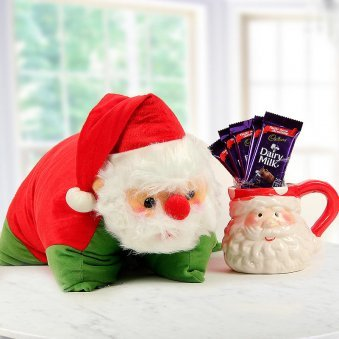 A Santa Pillow with a Santa Special Coffee Mug and 5 units of Cadbury Dairy Milk Chocolates