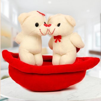 3 inches kiss me teddies standing on a Red swing