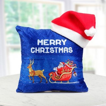 A 12x12 inches blue Christmas cushion displaying Santa on his Sleigh along with a Santa cap